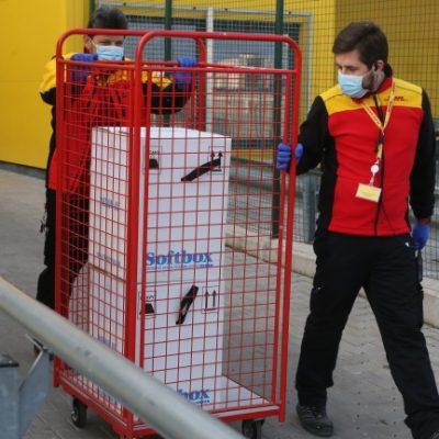 служител на DHL с ваксини Pfizer