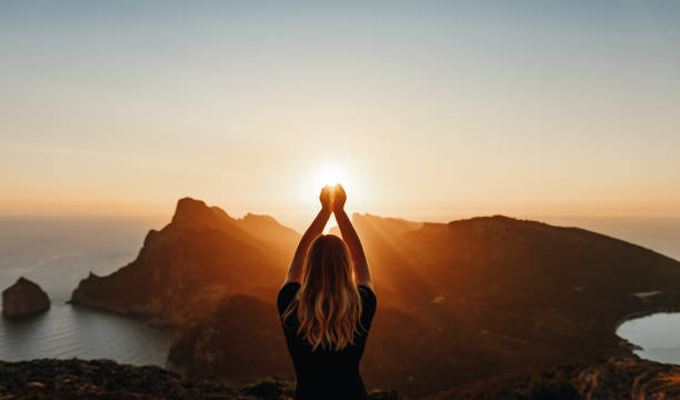 Young woman in spiritual pose holding the light in front of mountains
