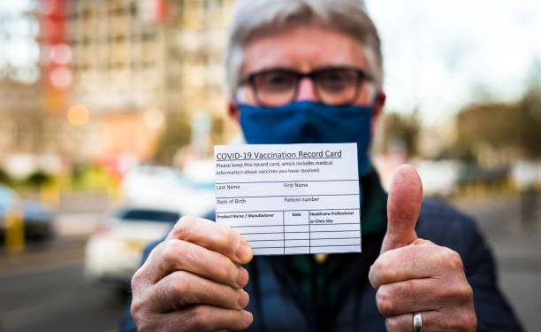 Close up color image depicting a senior man in his 70s holding a card outdoors in the city with details of his covid-19 vaccination. Focus on the card in the foreground while the man is defocused beyond. Room for copy space.