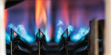 Flames ignited to heat water as seen through a gas boiler's viewing window.