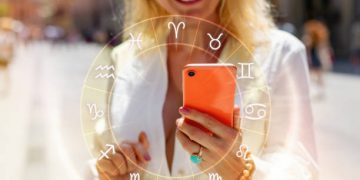 Concept of reading daily horoscopes on the phone; woman holding a phone and reading her daily horoscope