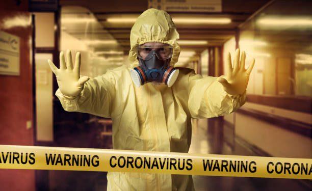 Coronavirus Warning cordon tape and men wearing protective suit
